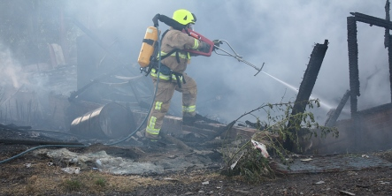 Firefighter with hose extinguishing a fire